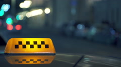 Illuminated Checkered Sighn of Taxi Cab in Night City Stock Footage