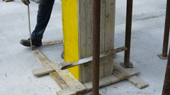 Worker reinforces the wooden formwork with steel ties Stock Footage
