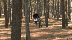 Father and son running through woods with paper airplane and than launch it Stock Footage