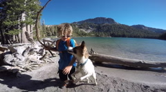 A boy throws a stick for a dog in a mountain lake. Stock Footage