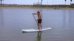 A man paddles his SUP stand-up paddleboard in a lake. Stock Footage