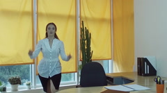 Working day. Pretty young brown-haired woman dancing at the desk in a office. HD Stock Footage