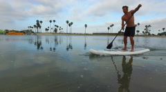 Tracking view of a man paddling his SUP stand-up paddleboard in a lake. Stock Footage