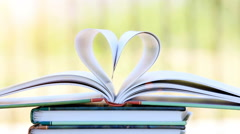 Book stack open page heart shape in wind, green garden background Stock Footage