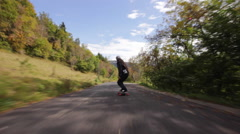 POV of young men longboard skateboarding downhill on a mountain road. Stock Footage