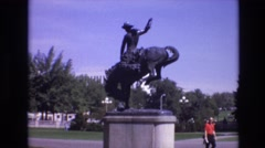 1974: statue of a cowboy riding a horse on a plinth a park with trees Stock Footage