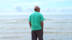 Asian senior man standing alone at the beach thinking about life Stock Footage