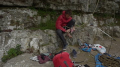 A man prepares to go rock climbing up a mountain by putting on his shoes. Stock Footage