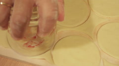 Woman using glass to cut circles of dough Stock Footage