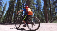 A boy rides his mountain bike on a singletrack dirt trail in the woods. Stock Footage
