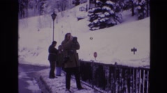 1974: guy taking pictures with his camera of the beautiful snow  Stock Footage