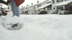 SLOW MOTION: Unrecognizable person removing snow off a snowy suburban street Stock Footage
