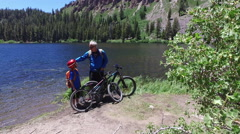 Portrait of a father and son with their mountain bikes near a lake. Stock Footage