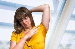 Woman with sweating under armpit in yellow dress in bussiness office Stock Photos