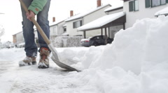 CLOSE UP: Man clearing fresh snow in front of the house in idyllic suburban town Stock Footage