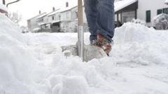 CLOSE UP: Man cleaning fresh snow from the front yard in idyllic suburbia Stock Footage