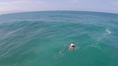 Aerial view of a man sitting on his board waiting for waves while sup stand-up p Stock Footage