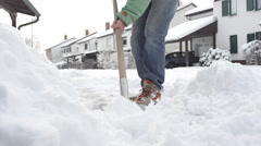 CLOSE UP: Man cleaning fresh snow from the driveway in idyllic suburbia Stock Footage