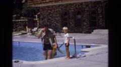 1973: father with cute child near swimming pool wearing unbuttoned shirt Stock Footage