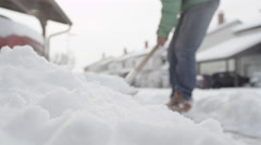 CLOSE UP: Male working, shoveling winter snow from the sidewalk, making pile Stock Footage