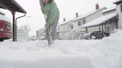 CLOSE UP: Residents shoveling fresh winter snow from the sidewalk and frontyards Stock Footage