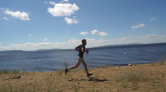Male runner runs along the river Stock Footage