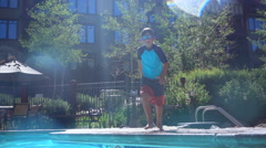 A boy jumps and does a cannonball into a pool at a hotel resort. Stock Footage