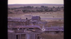 1973: man walks through abandoned rural town with dilapidated buildings  Stock Footage