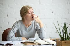 Portrait of a yawning student girl at the desk Stock Photos