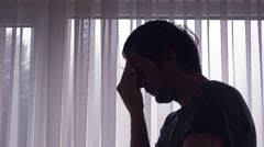 Silhouette of sad depressive man by the window Stock Footage