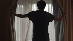 Man in dark hotel room opening curtains on window Stock Footage