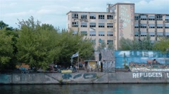 Pant establishing shot of graffiti on the embankment of Spree, Berlin Stock Footage