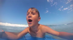 POV view of a boy body boarding in the waves at the beach. Stock Footage