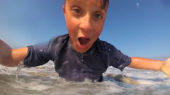 POV view of a boy body boarding in the waves at the beach, super slow motion. Stock Footage