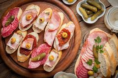 Tapas with sliced sausage, salami, olives and parsley on a wooden table. Stock Photos