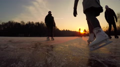 FPV LOW ANGLE: Happy teenagers iceskating and playing hockey at magical sunset Stock Footage