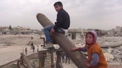 Syria, Kobani - February, 2016: Boy sitting on bomb Stock Footage