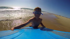 POV view of a boy wearing goggles while body boarding in the waves at the beach. Stock Footage