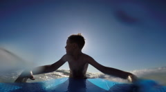 POV view of a boy body boarding in the waves at the beach, slow motion. Stock Footage