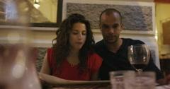 4K Attractive mixed race couple drinking wine in Italian restaurant Stock Footage