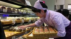 Motion of worker putting cake on display rack inside Saint Germain bakery Stock Footage