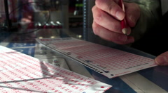 Woman hands filling lucky number on 6/49 lottery ticket. Stock Footage