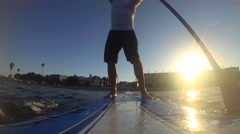 POV of a man paddling an SUP stand-up paddleboard on a lake at sunset, time-laps Stock Footage