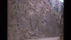 1968: traveling on a dirt road out of a rock walled canyon  Stock Footage