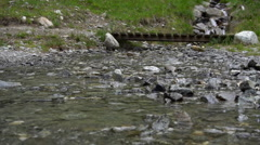 A mountain stream river with a bridge in the background, slow motion. Stock Footage