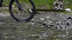 Two mountain bikers ride through a stream instead of taking the bridge. Stock Footage