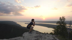A man crouches on top of a mountain Stock Footage