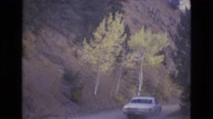 1968: a white car moving through a ghat road flanked by trees COLORADO SPRINGS Stock Footage