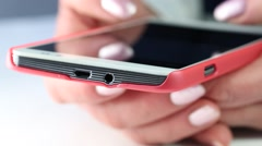 Woman types sms on smartphone. Close up of woman hands with red smartphone Stock Footage