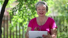 Blonde woman sits on the chair in garden and communicates via tablet computer Stock Footage